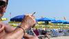 Кальяри: турист тушит сигарету в пляжном песке - полиция штрафует нарушителя на